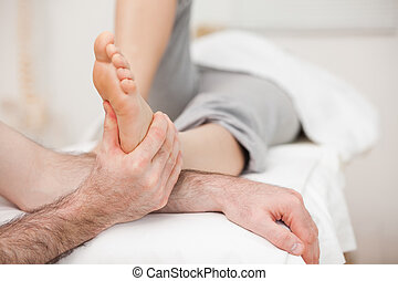 Woman having a foot massage while bending a leg in a medical...