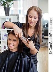 Woman Having a Haircut - Pretty young woman getting a hair ...