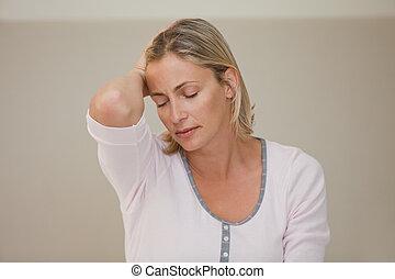 Woman having a headache at home