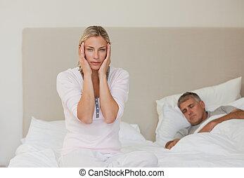 Woman having a headache while her husband is sleeping