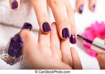Woman having a nail manicure in a beauty salon with a ...
