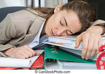 woman having a nap on top of the folders