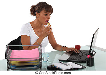 Woman having a snack whilst sat at desk