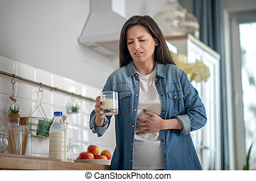 Woman having a stomach ache after drinking milk