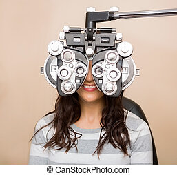 Woman Having An Eye Test - Happy young woman looking through...