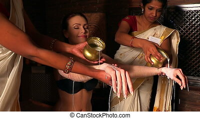 Woman having Ayurvedic spa treatment. Indian masseuse pouring oil of patient.