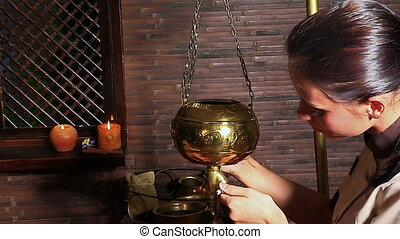 Young woman having Ayurveda spa treatment. Masseuse pouring oil on head of client.