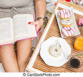 woman having breakfast in bed while reading a book