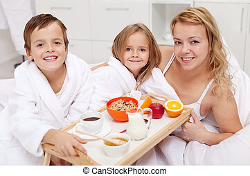 Woman having breakfast in bed with the kids