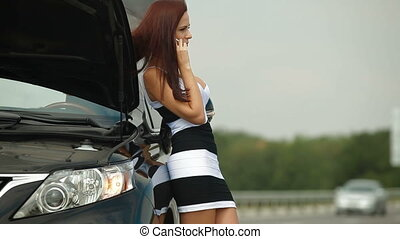 Woman having car troubles on the road calling for emergency repair service