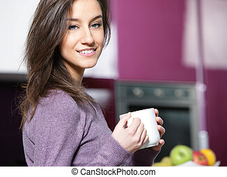 woman having coffee at the kitchen