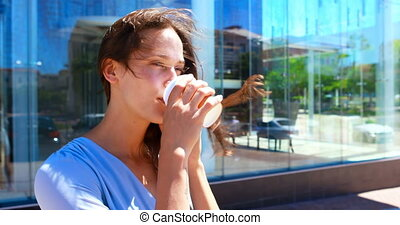 Woman having coffee while talking on mobile phone 4k