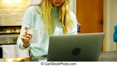 Woman having coffee while using laptop in kitchen 4k