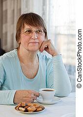 Woman having coffee with cookies