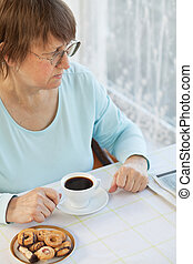 Woman having coffee with cookies