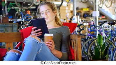 Woman having cold coffee while using digital tablet at workshop 4k