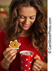 Woman having cup of chocolate and cookie in Christmas kitchen