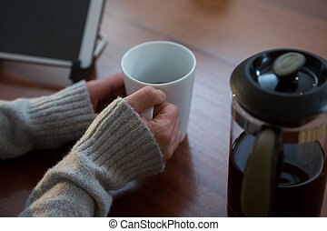 Woman having cup of coffee at home