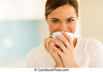 woman having cup of coffee in the kitchen