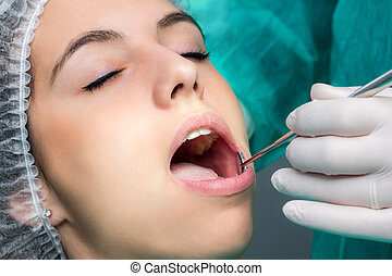 Woman having dental operation.