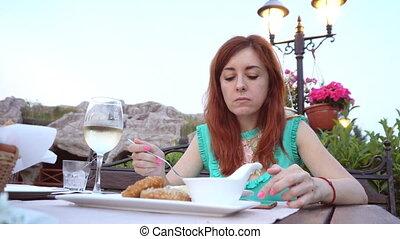 woman having dinner in the restaurant on the street