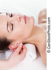 Woman having ear massage