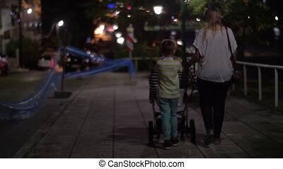 Woman having evening walk with children