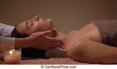 woman having face and head massage at spa - wellness, beauty...