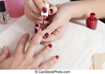 Woman Having Fingernails Painted At Beauty Salon