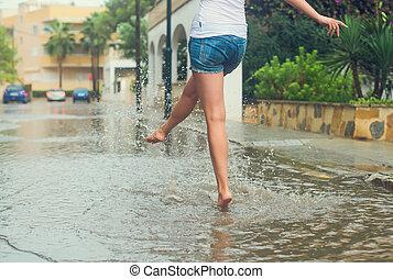 Woman having fun on the street after the rain.