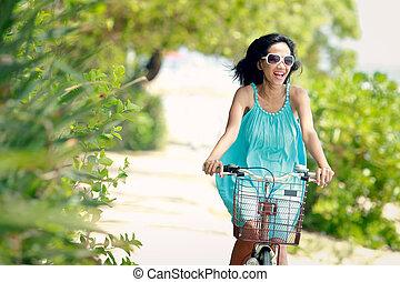 woman having fun riding bicycle at the beach