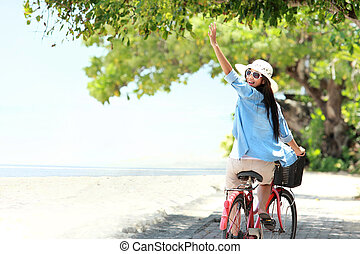 carefree woman having fun riding bicycle and raised her arm at the beach