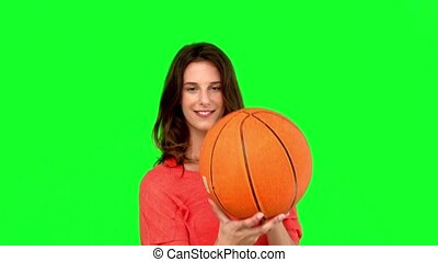 Woman having fun with a basket ball on green screen in slow...