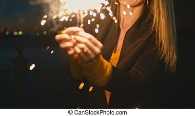 Woman having fun with burning bengal-light sparklers in her hands