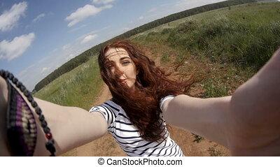 Woman having fun with camera on field