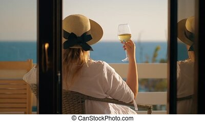 Woman having good time drinking wine at the balcony overlooking sea