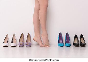 Woman having hard time choosing. Beautiful woman legs,...