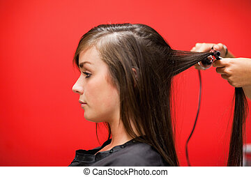 Woman having her hair straightened