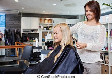 Woman Having Her Hair Styled - Young woman having her hair...