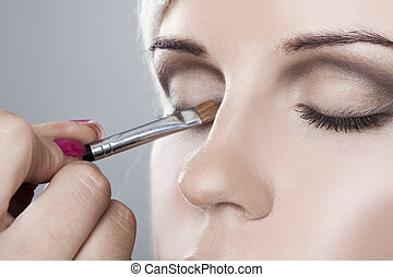 Woman having her makeup applied close-up for eyes