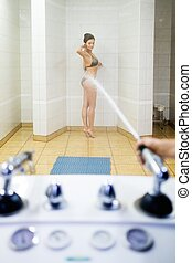 Woman having high pressure massage with shower
