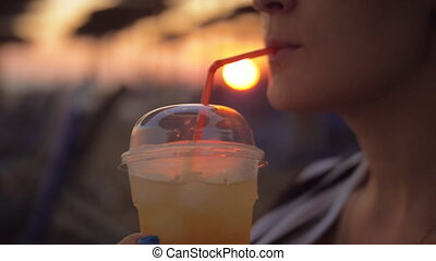 Woman having iced drink on the beach at sunset - Slow motion...