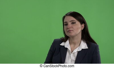 Woman having job interview or other serious conversation against green screen