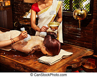 Woman having massage with pouch of rice. - Woman having...