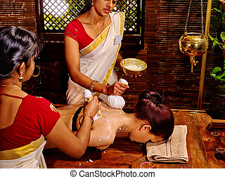 Woman having massage with pouch of rice. - Woman having ...