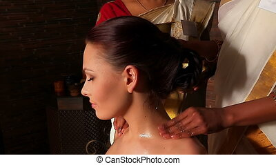 Woman having neck Ayurveda spa treatment. Professional masseurs hands to slide on neck and shoulders of patient.