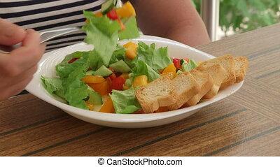 Woman having outside light lunch on the balcony eating fresh vegetable salad
