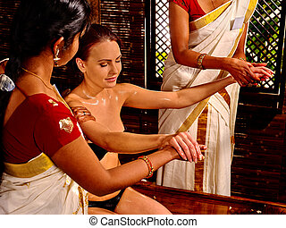 Woman having pouring oil massage in spa Indian salon.