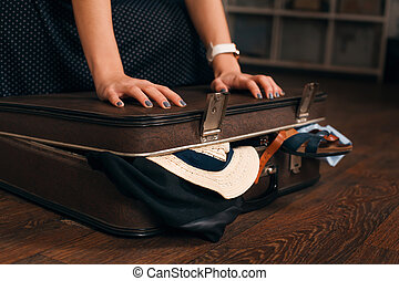 Woman having problem with closing a suitcase.