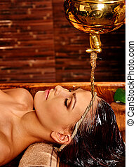 Woman having Shirodhara pouring oil on head in India spa . -...